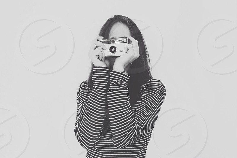 woman wearing black and white stripe long sleeve top holding a camera photo