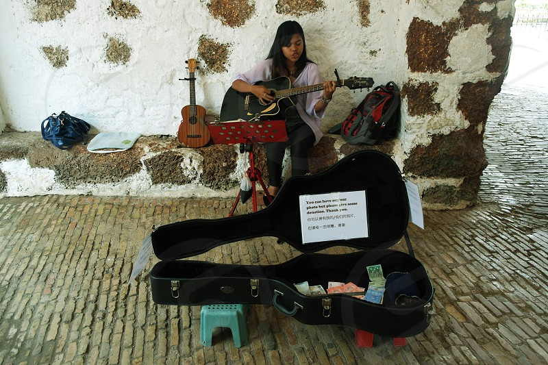 woman in black pants playing black acoustic guitar photo