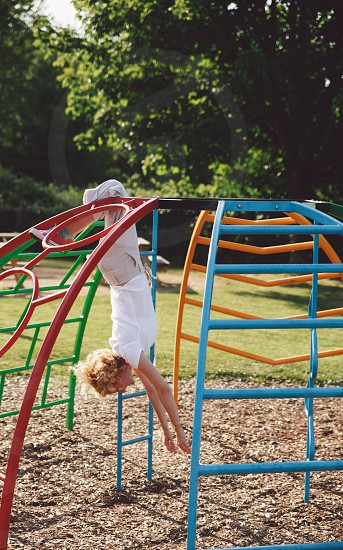 girl in white cap sleeve shirt hanging upside down in a playground dome during daytime photo