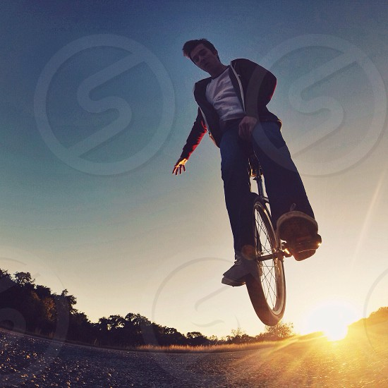 man in black jacket white inner shirt and blue jeans riding a unicycle doing stunt at sunrise view during daytime photo