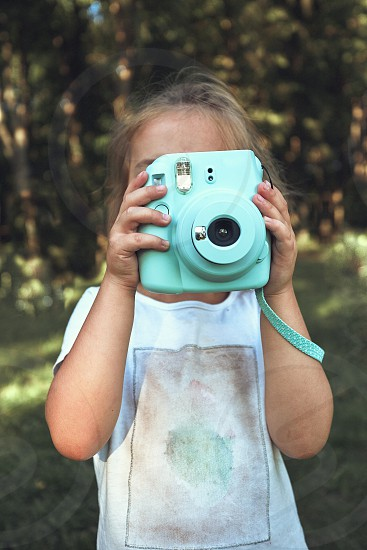 Little girl taking photo using instant camera. Candid people real moments authentic situations photo