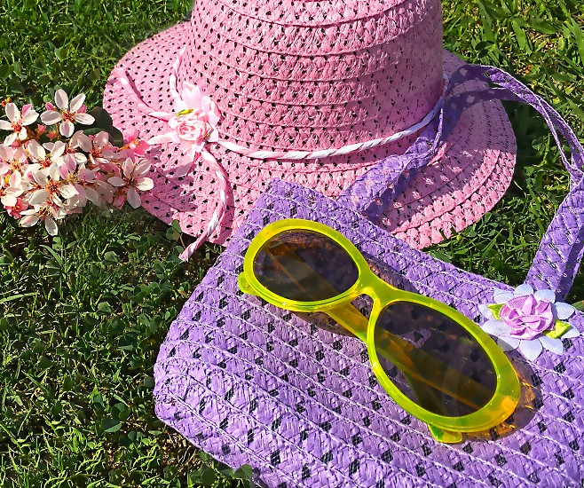 Child's pink straw hat purple purse and yellow sunglasses arranged on the green grass photo