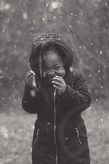 smiling brunette child wearing hooded winter coat standing beneath falling snow in black and white photo