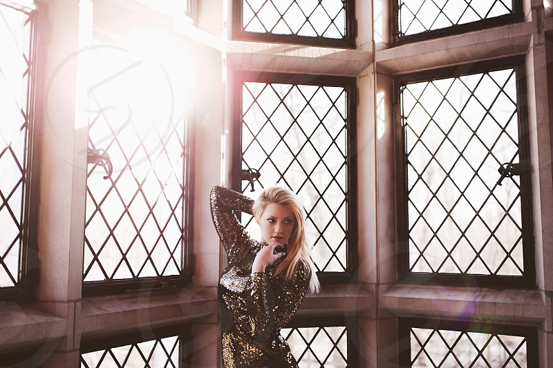 blonde woman standing by lattice windows photo