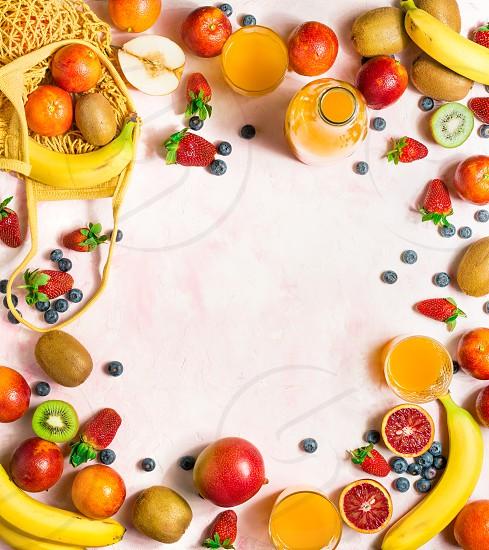 Abundant fresh fruit and orange juice on a pink background photo