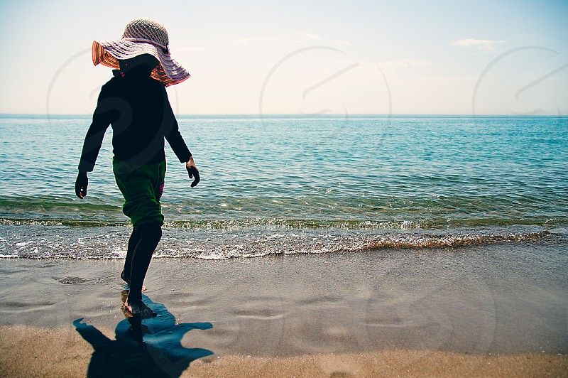 A child wearing a hat and walking on the beach. photo