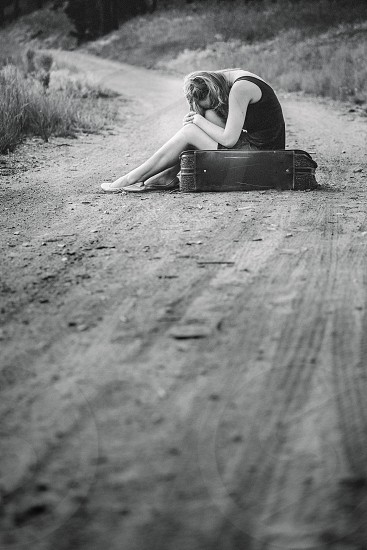 woman sitting on a suitcase on a dirt road photo