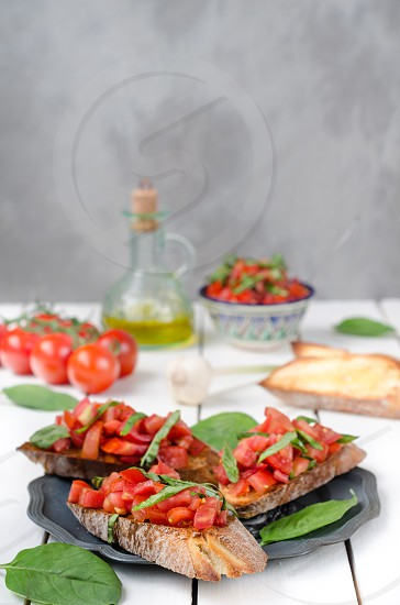 Italian bruschetta with tomatoes and basil on old plate with ingredients on light background photo