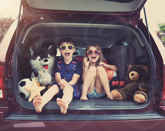 Happy Children are sitting in the back of a car with travel objects waiting to go on a vacation. Use it for a family holiday lifestyle concept. photo