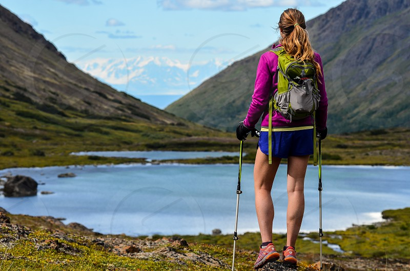 A woman stares off over a lake in the wilderness area behind Anchorage Alaska photo