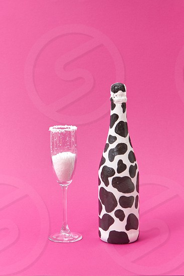 Holiday glass of white powder as a sugar and creative painted bottle with black spots on a hot pink background copy space. Congratulation card. photo