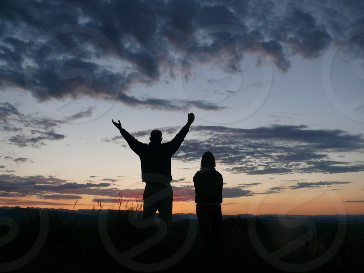 silhouettes of 2 people standing outside under cloudy sky at sunrise photo