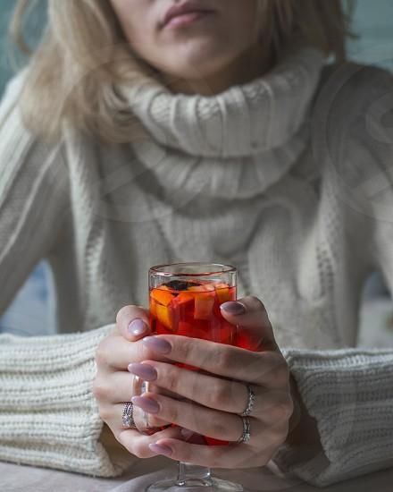 Beautiful girl in a warm sweater holding hot mulled wine in her hands. photo