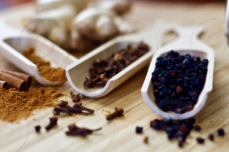 Health & Wellness - Closeup of ground cinnamon and cinnamon sticks ginger root whole cloves and dried elderberries in wooden scoops on a wooden surface as ingredients for homemade elderberry syrup photo