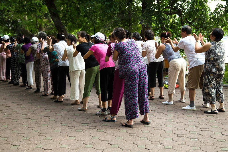 Group Massage at Hoan Kiem Lake - lakeside pavements serve as a focal point for Hanoi public life.  It is a popular spot for jogging exercising and early morning tai chi sessions along its banks including this group giving each other a massage. photo