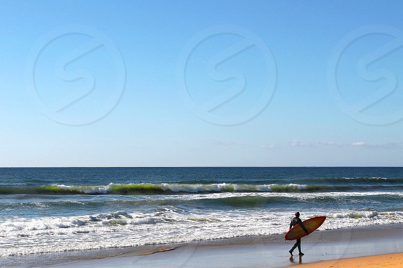 Surfer in a wetsuit carries a board and walks down an empty beach looking at the waves. photo
