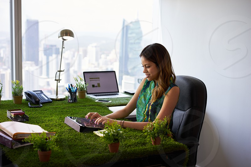 woman; working; typing; email; tablet; office; grass; plant; person; ecology; green; happy; environment; adult; app; attractive; botany; business; businessperson; businesswoman; cheerful; company; computer; concept; corporate; desk; ecologist; employee; environmental; environmentalist; garden; harmony; hispanic; internet; keyboard; lifestyle; messaging; nature; people; skyscraper; table; technology; wifi; window; work; worker; workplace; writing; young; zen photo