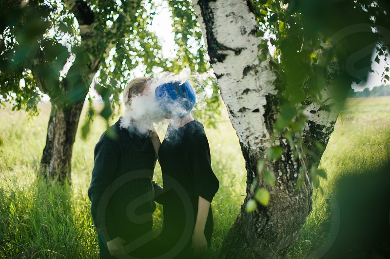 young couple with dyed hair smoking electronic cigarettes photo