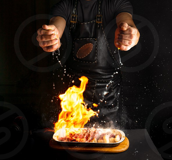 Restaurant chef grilling meat adding lemon juice to the dish photo