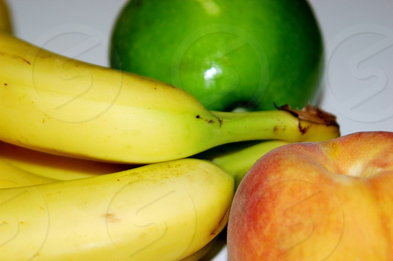 A collection of fruit including an apple bananas and a peach photo