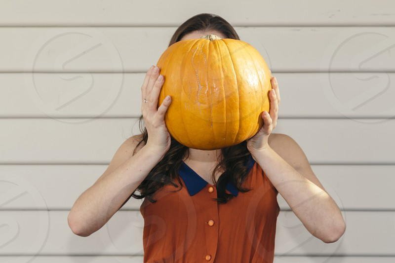 pumpkin halloween hallowe'en autumn fall harvest thanksgiving young brunette girl woman holding in front of face photo