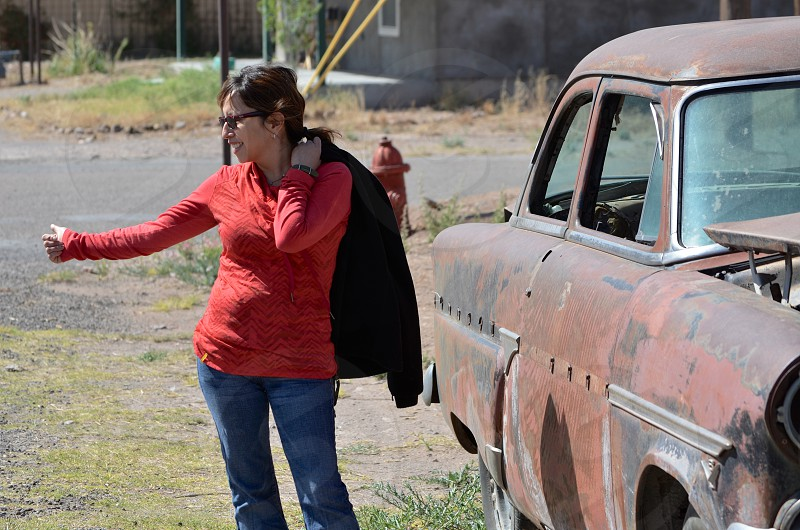 A woman hitchhiking next to a broken-down old Chevrolet rusting in the Sun of Marfa TX. photo