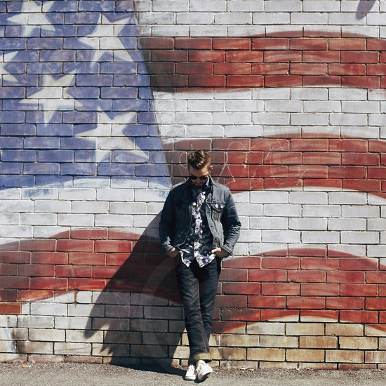 man in gray denim jacket leaning on american flag painted wall photo