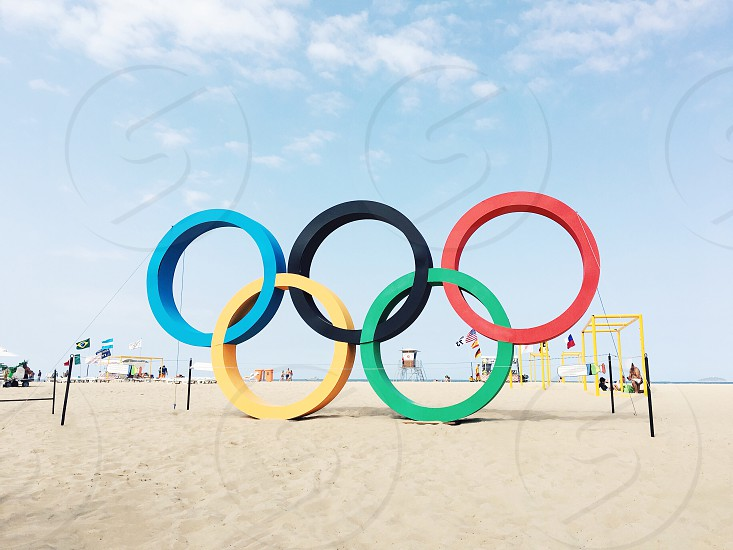 rio olympics logo on white beach under blue cloudy sky during daytime photo