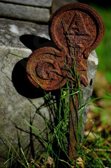 Rust emblem in stuck in ground photo
