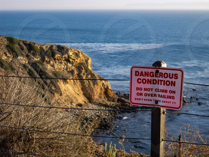 Warning sign at the edge of a steep cliff on the Palos Verdes Peninsula near Los Angeles on the edge of the Pacific Ocean has a slightly humorous tone. photo