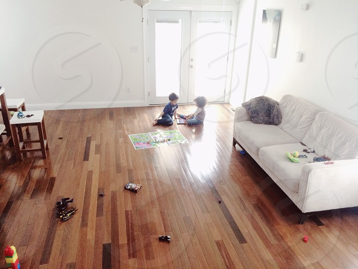 2 boy playing in brown wooden floor photo