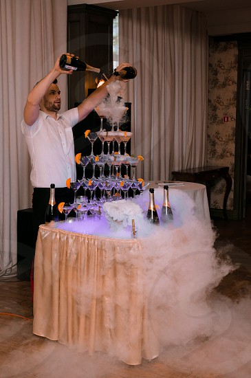 bartender pouring some champagne on pyramid form of cocktail glasses photo