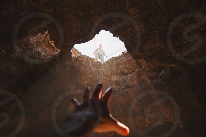first person view of man reaching out towards the man wearing gray shirt and pants standing on top of the cave near the hole during daytime photo