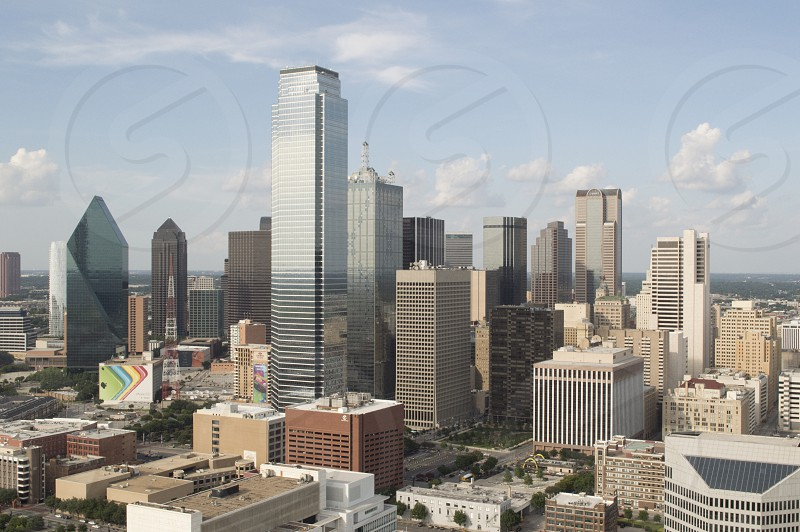 Skyline of Dallas Texas as seen from about 500 feet up on a sunny day with a few light clouds in the sky behind the skyscrapers. photo