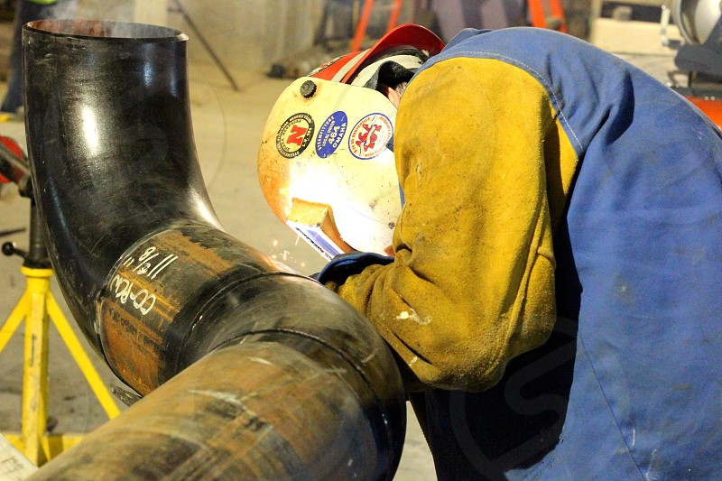 Man weld welding welder hat cap indoors yellow green bright hot work working worker construction Union labor protection America photo