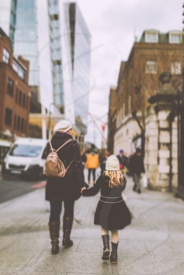person carrying brown backpack and girl in white knit cap holding hands while walking on the sidewalk photo