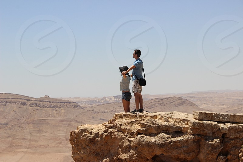 man and woman standing on mountain photo