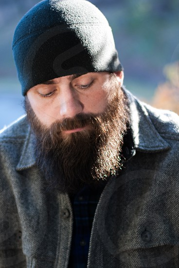 Bearded man with beanie looking down photo