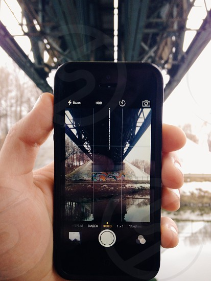 person standing under bridge holding black iphone showing exact photo of view photo