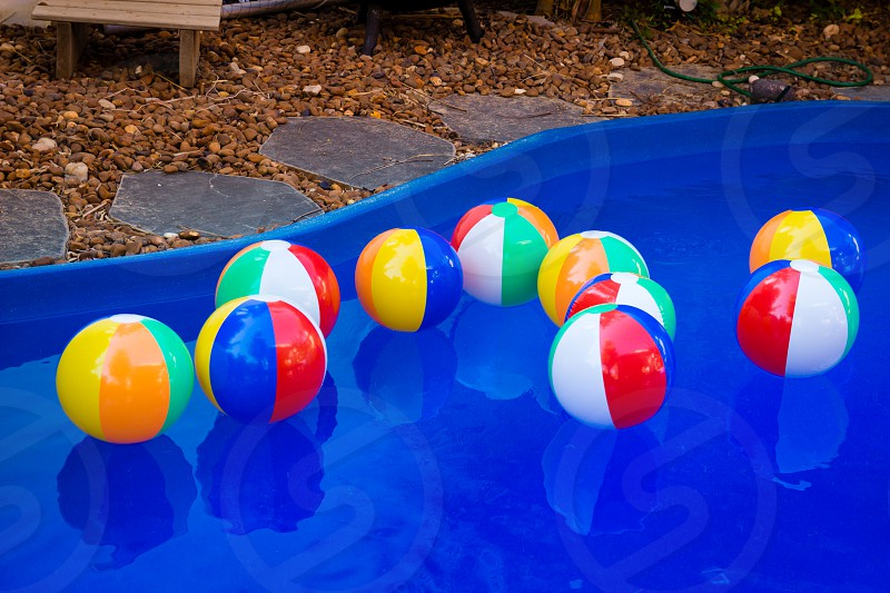 Colorful beach balls floating in pool. photo