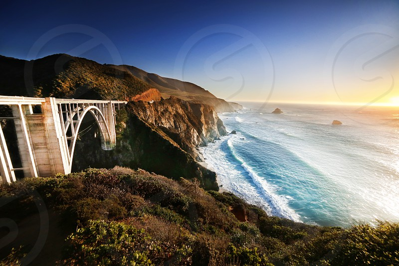 white steel bridge connecting two mountains near ocean during sunset photo