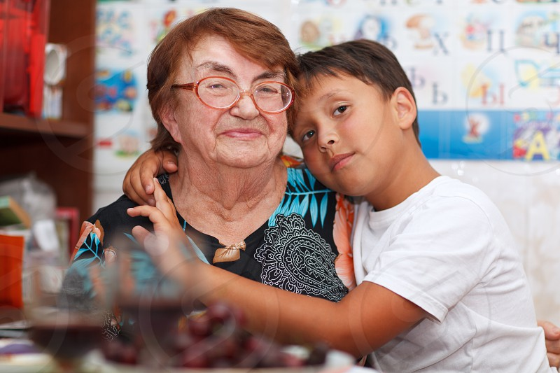 Grandson is hugging his grandmother looking to the camera photo