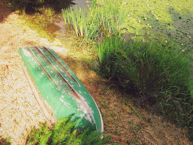 green rowboat on the bank of the lake upside down photo