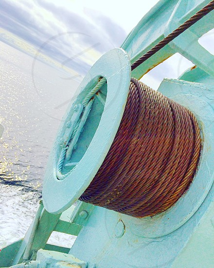 rusty metal cable on green reel with water under photo