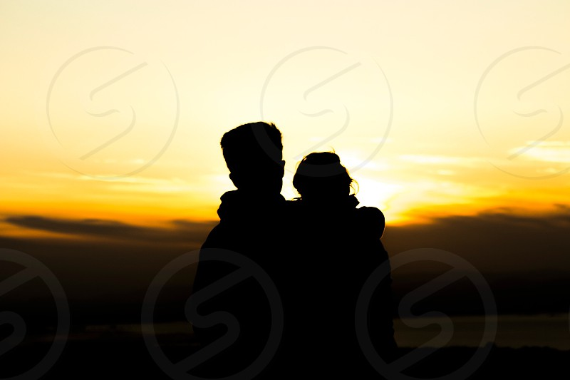 man and woman silhouette through sunlight photo