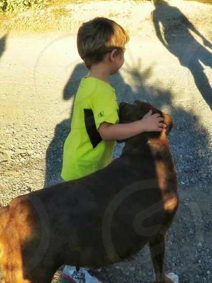 A young boy in a yellow shirt loves his dog. The dog loves his young boy. Mom is in the shadows watching closely. Real love.  photo