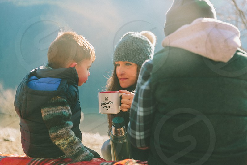 A little boy blowing on a cup of hot chocolate while camping in the mountains with his family.  photo