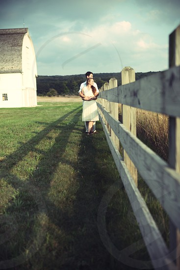 couple embracing on ranch wearing white dress photo