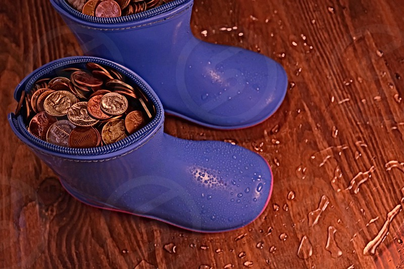 saving for a rainy day  rain boots filled with coins photo