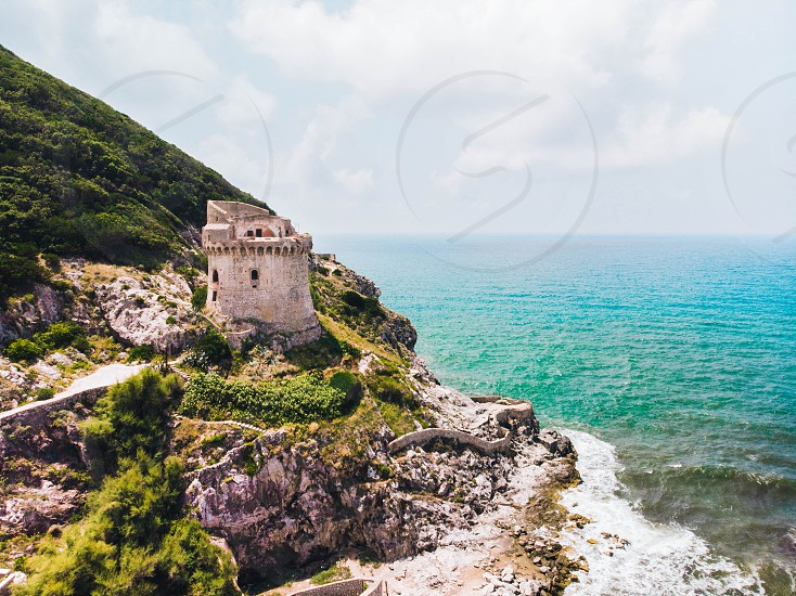 Beautiful scene old building. Ancient defense tower on mountain in the Mediterranean sea. Paola tower is placed on Circeo promontory of Sabaudia Italy. View from drone aerial. photo